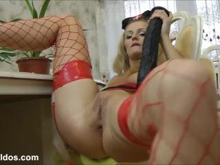 Blonde in nurse uniform shoving a long black dildo in her asshole