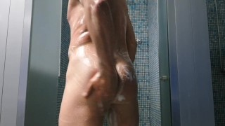 Muscular guy washes in the shower of the gym