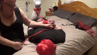 Man hogtied and gagged by woman on bed and struggling to get free