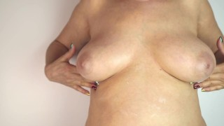 an elderly 60 year old woman smears her large Breasts with large areola nipples with cream