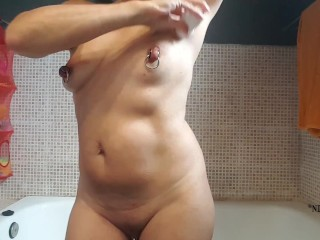 naked in the bathroom putting some body oil on my body showing my xxl nipple piercings & pussy rings