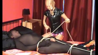 Pantyhose mistress encased in shiny tights and her black zentai male slave for bondage and handjob