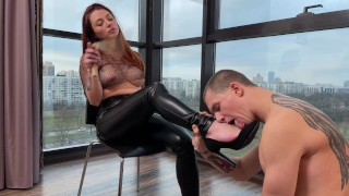The mistress spanks her slave with a rattan and pokes his heel on the chest