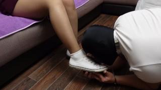 Раб в наручниках одевает носочки на ножки госпожи в колготках и лижет кеды