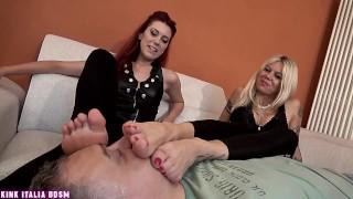 Dominato dalle due amiche la rossa e la bionda milf annusa i loro piedi sudati e odorosi