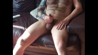 Hairy tattooed man long wank and big cum watching porn